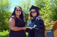 Dr. Alaí Reyes-Santos gives the Alumni Award to a distinguished alum.